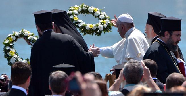 Papa Francesco e il Patriarca di Costantinopoli gettano delle corone di fiori in mare in memoria dei migranti morti nel tentativo di raggiungere l'isola di Lesbo. dox Patriarch Barthol(LOUISA GOULIAMAKI/AFP/Getty Images)